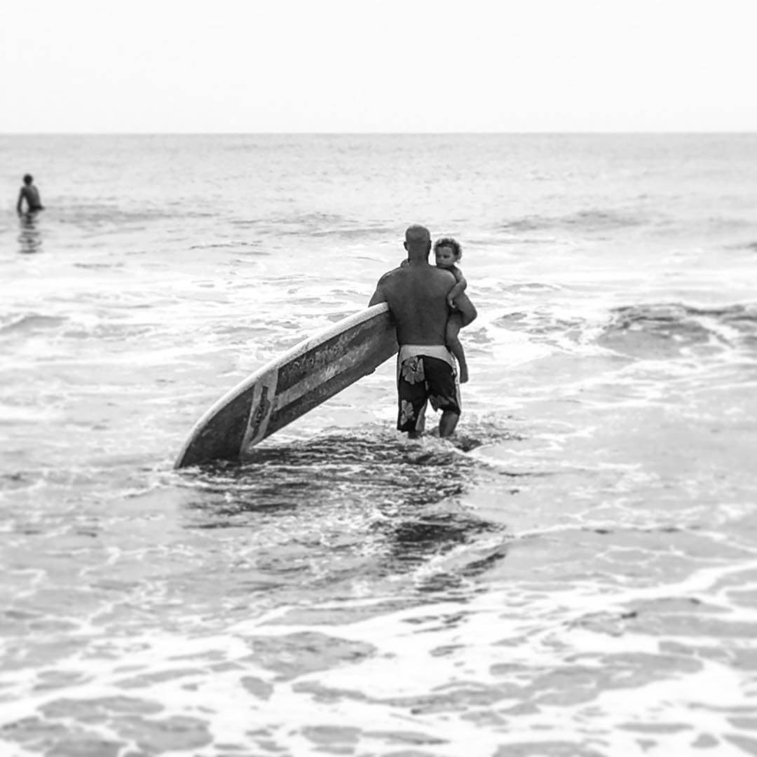 man carrying child into ocean