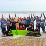 group of mostly kids in wetsuits in front of surboard on surf beach