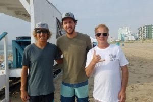 three surfer dudes on beach